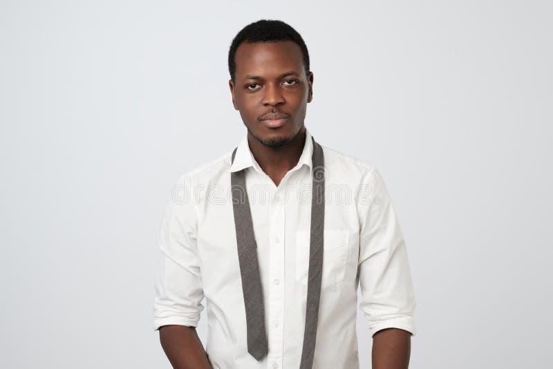 ο αφρικανικός τύπος στο άσπρο πουκάμισο που στέκεται μετά από τη σκληρό εργάσιμη ημέρα ή το κόμμα Δεν ξέρω πώς να φορέσω το δεσμό στοκ εικόνες με δικαίωμα ελεύθερης χρήσης