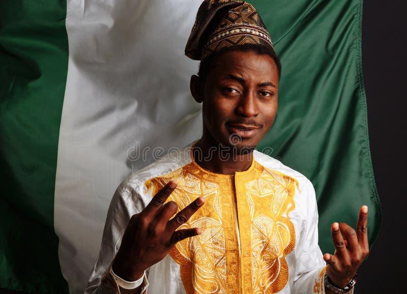 Ο Αφρικανός με παραδοσιακά ρούχα ποζάρει μπροστά στην κάμερα, χαμογελά και διασκεδάζει Πριν από τη σημαία της νιγηρίας στοκ εικόνα με δικαίωμα ελεύθερης χρήσης