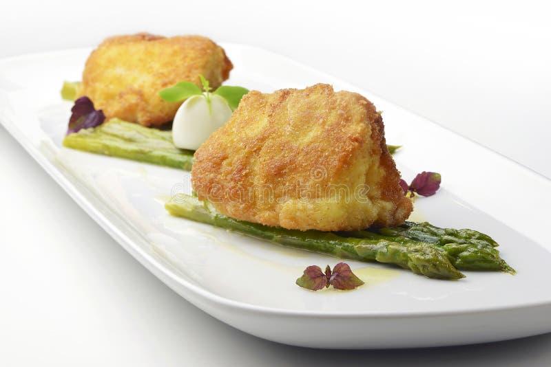 Ο αλατισμένος βακαλάος πιάτων ψαριών πασπάλισε το Milanese ύφος με το σπαράγγι με ψίχουλα στοκ εικόνα με δικαίωμα ελεύθερης χρήσης