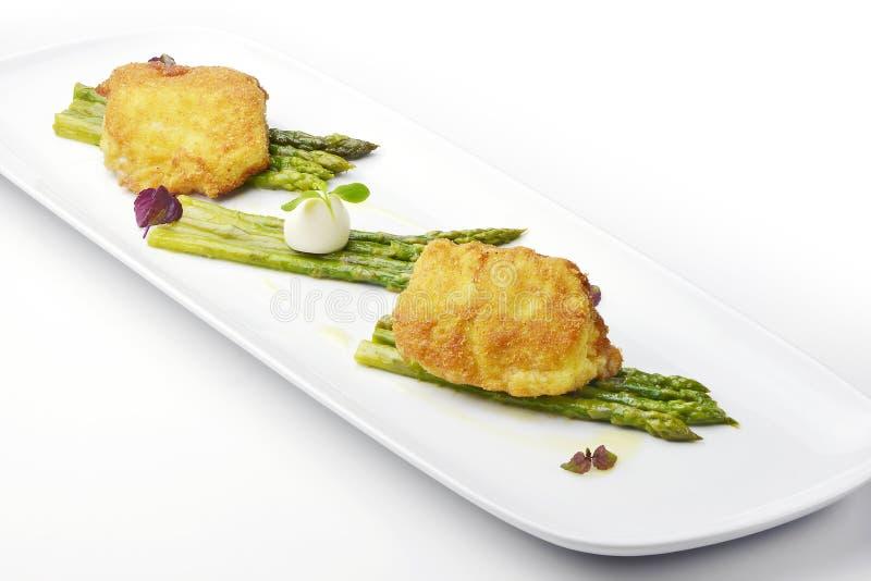 Ο αλατισμένος βακαλάος πιάτων ψαριών πασπάλισε το Milanese ύφος με το σπαράγγι με ψίχουλα στοκ φωτογραφίες