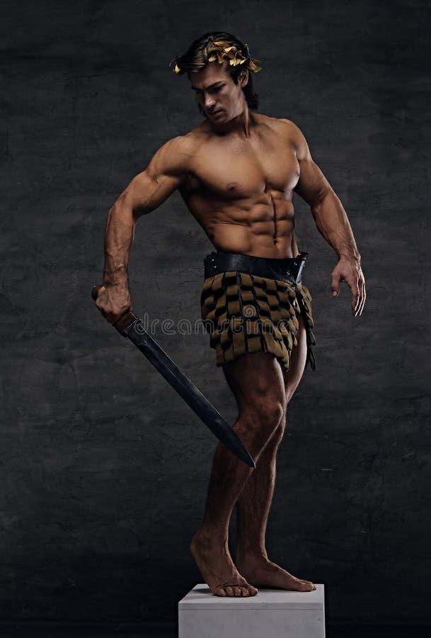 Ο βάναυσος αρχαίος αθλητής-πολεμιστής της Ρώμης κρατά ένα ξίφος στοκ φωτογραφία με δικαίωμα ελεύθερης χρήσης