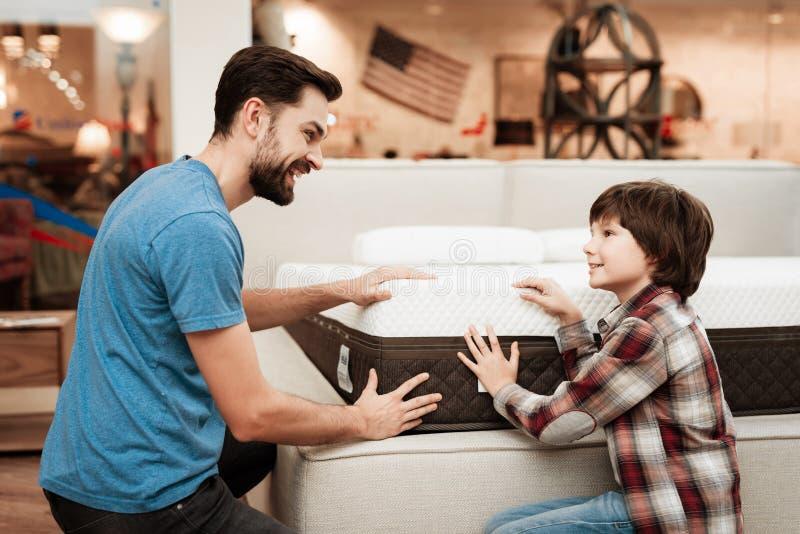Ο βέβαιος γενειοφόρος πατέρας με το μικρό αγόρι επιλέγει το ορθοπεδικό στρώμα στο κατάστημα επίπλων στοκ φωτογραφία