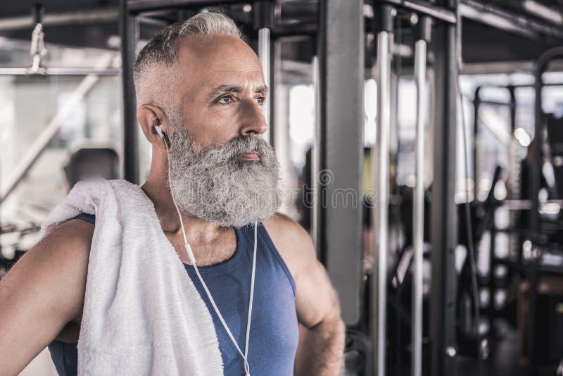 Ο βέβαιος μοντέρνος συνταξιούχος σκέφτεται στεμένος στο αθλητικό κέντρο στοκ εικόνες