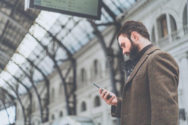 Ο βέβαιος όμορφος επιχειρηματίας έντυσε στα μοντέρνα ενδύματα που το μήνυμα το κινητό τηλέφωνό του στην αίθουσα του σιδηροδρόμου στοκ εικόνα με δικαίωμα ελεύθερης χρήσης