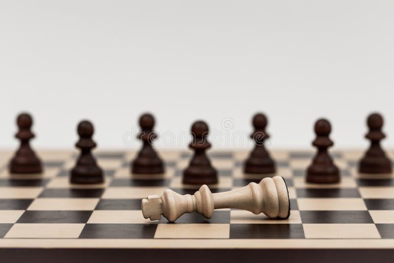 Ο βασιλιάς στο σκάκι έχει πέσει σε διάφορα ενέχυρα στοκ εικόνες
