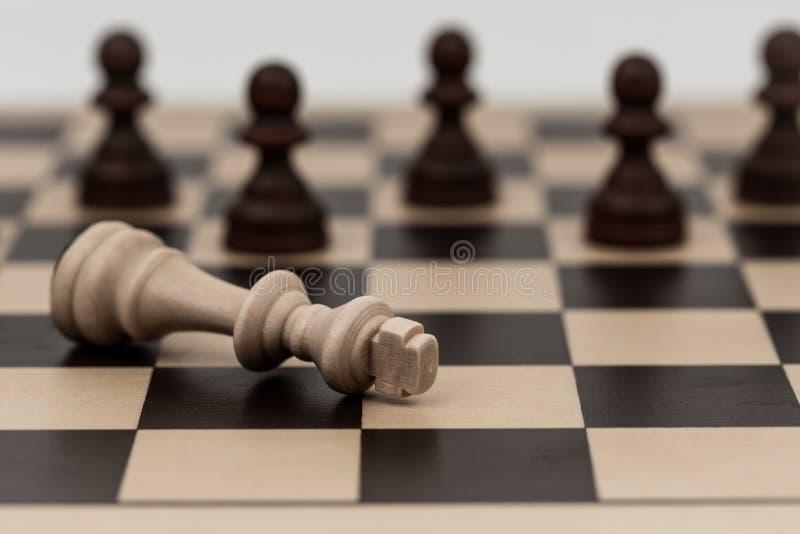 Ο βασιλιάς στο σκάκι έχει πέσει σε διάφορα ενέχυρα στοκ φωτογραφία