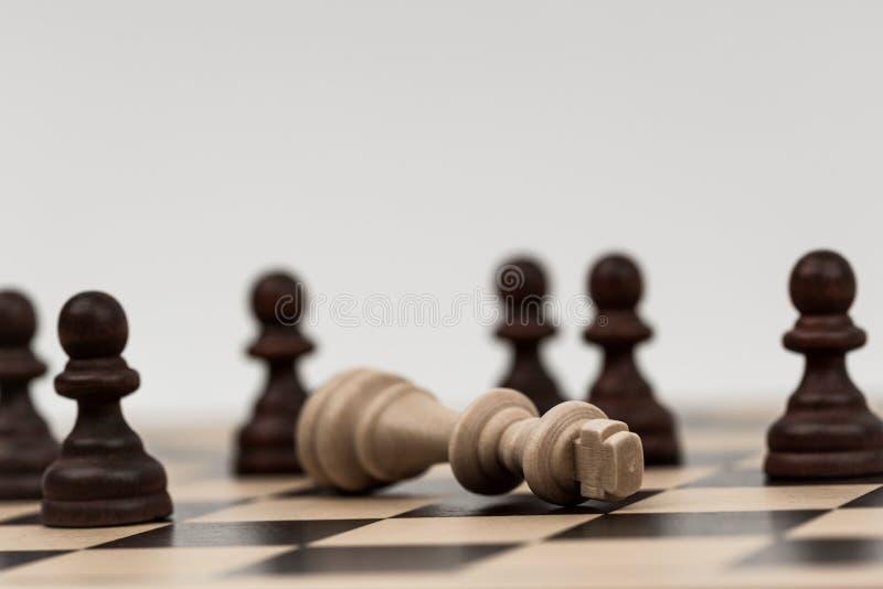 Ο βασιλιάς στο σκάκι έχει πέσει σε διάφορα ενέχυρα στοκ εικόνα