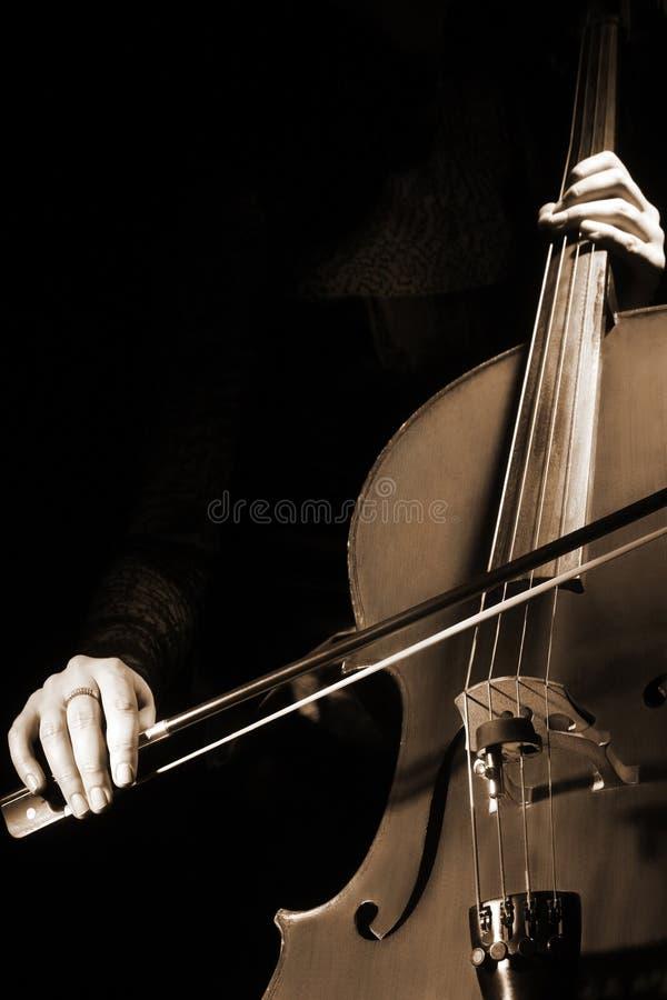 Ο βιολοντσελίστας φορέων βιολοντσέλων δίνει το βιολοντσέλο παιχνιδιού με το τόξο στοκ εικόνα με δικαίωμα ελεύθερης χρήσης