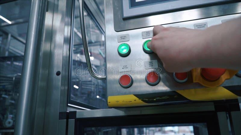 Ο βιομηχανικός εργάτης πιέζει το κουμπί στο σημείο ελέγχου και αρχίζει το μεταφορέα της γραμμής παραγωγής, πρώτη άποψη προσώπων σ στοκ εικόνες