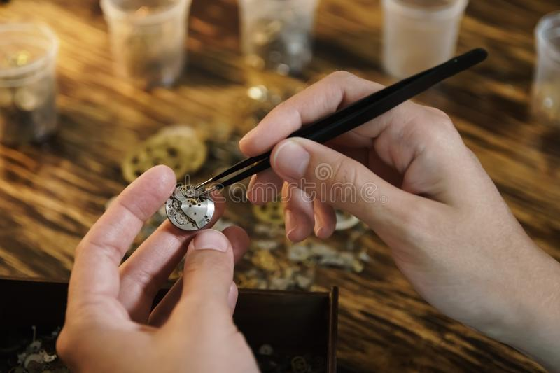 Ο βιοτέχνης αποσυναρμολογεί το ρολόι και παίρνει τα εργαλεία στοκ φωτογραφία