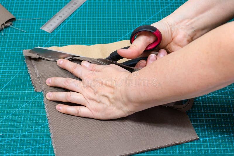 Ο βιοτέχνης κόβει το ύφασμα για τις τσάντες χρησιμοποιώντας το σχέδιο στοκ εικόνες