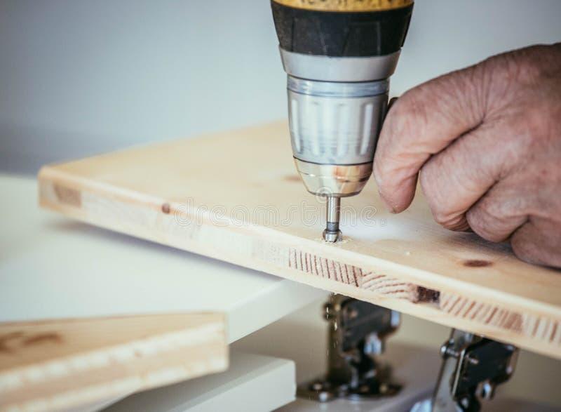 Ο βιοτέχνης τρυπά με τρυπάνι στο ξύλο με τη μηχανή διατρήσεων στοκ εικόνες