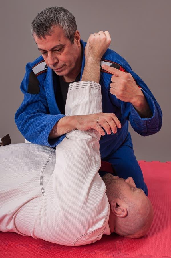 Ο βραζιλιάνος εκπαιδευτικός jitsu jiu καταδεικνύει το βραχίονα επίγειας πάλης στοκ εικόνες με δικαίωμα ελεύθερης χρήσης