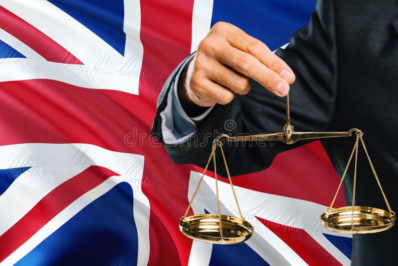Ο βρετανικός δικαστής κρατά τις χρυσές κλίμακες δικαιοσύνη με υπόβαθρο Ηνωμένων το κυματίζοντας σημαιών Θέμα ισότητας και νομική  στοκ φωτογραφίες με δικαίωμα ελεύθερης χρήσης