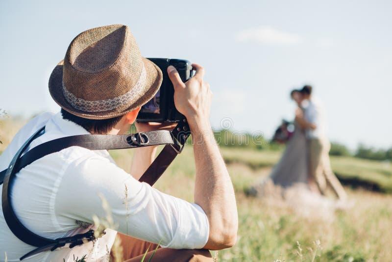Ο γαμήλιος φωτογράφος παίρνει τις εικόνες της νύφης και του νεόνυμφου στη φύση, φωτογραφία Καλών Τεχνών στοκ εικόνα