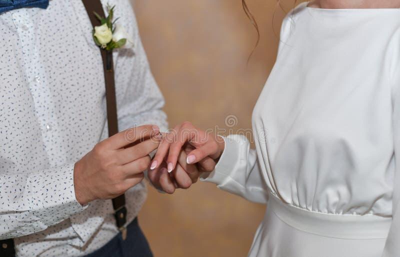 Ο γαμπρός βάζει το δαχτυλίδι στο δάχτυλο της νύφης στο γάμο στοκ φωτογραφίες
