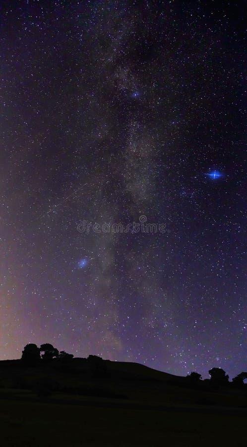 Ο γαλακτώδης τρόπος που φθάνει επάνω στο νυχτερινό ουρανό επάνω από το Hill μελιού στοκ εικόνα