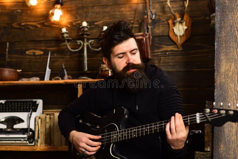 Ο γενειοφόρος μουσικός ατόμων απολαμβάνει προετοιμάζοντας την απόδοση στο σπίτι, ξύλινο υπόβαθρο Ωθήστε τις δεξιότητές σας Τύπος  στοκ εικόνες