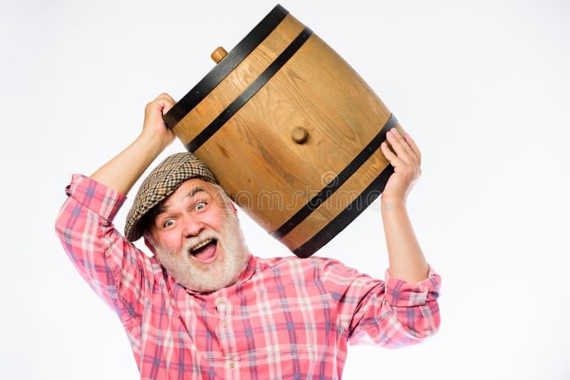 Ο γενειοφόρος πρεσβύτερος ατόμων φέρνει το ξύλινο βαρέλι για το άσπρο υπόβαθρο κρασιού Παραγωγή της οικογενειακής παράδοσης κρασι στοκ φωτογραφία με δικαίωμα ελεύθερης χρήσης