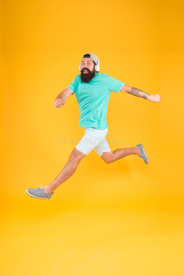 Ο γενειοφόρος τύπος απολαμβάνει τη μουσική Βίαια μετακίνηση Χορεύοντας συσκευή ακουστικών άλματος Hipster Ενθαρρυντικό τραγούδι Β στοκ εικόνα