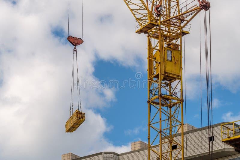 Ο γερανός πύργων κίτρινος παίρνει τα οικοδομικά υλικά στην οικοδόμηση του multi-storey σπιτιού, θερινή ημέρα στοκ φωτογραφία με δικαίωμα ελεύθερης χρήσης