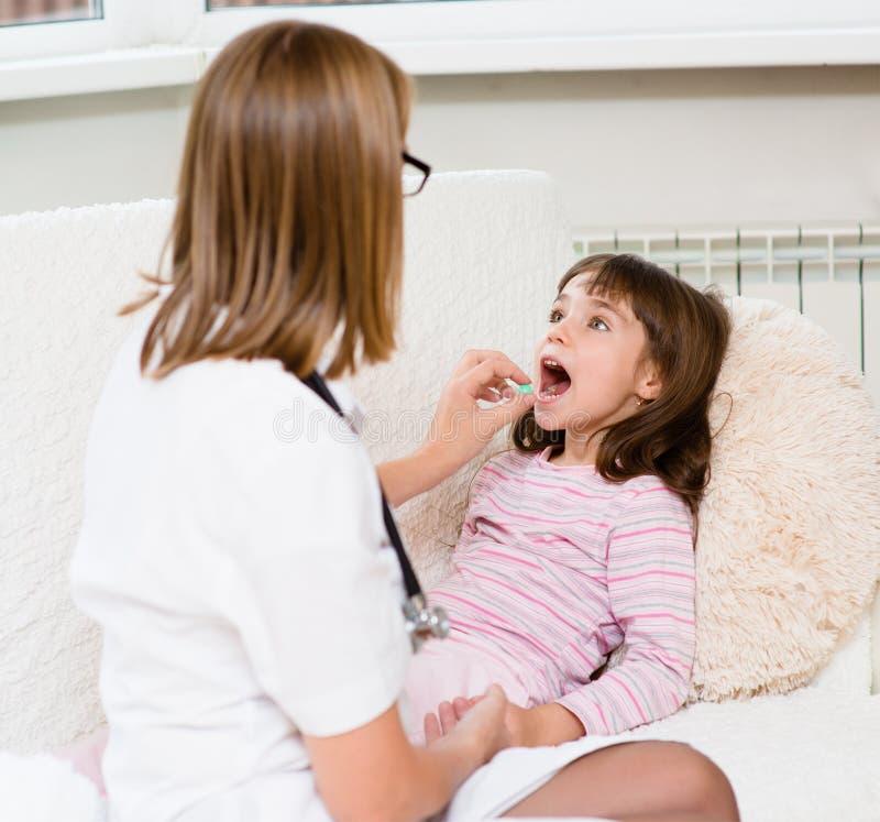 Ο γιατρός δίνει την ταμπλέτα στο άρρωστο παιδί στοκ εικόνες