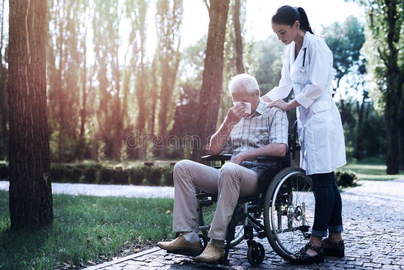 Ο γιατρός ανακουφίζει το φωνάζοντας ηληκιωμένο στο θερινό πάρκο στοκ φωτογραφία