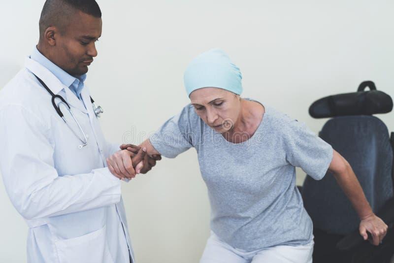 Ο γιατρός βοηθά μια γυναίκα που υποβάλλονται στην αποκατάσταση αφότου σηκώνεται η θεραπεία του καρκίνου από μια αναπηρική καρέκλα στοκ φωτογραφίες