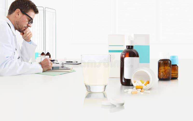 Ο γιατρός γράφει την ιατρική συνταγή σε ένα γραφείο γραφείων με τις ταμπλέτες της aspirin γυαλιού, τα χάπια και τα μπουκάλια φαρμ στοκ φωτογραφίες
