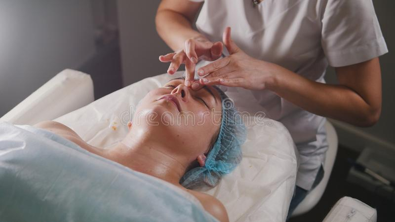 Ο γιατρός γυναικών εκτελεί την καλλυντική διαδικασία - καλύψτε το του προσώπου μασάζ στο σαλόνι SPA skincare στοκ εικόνες