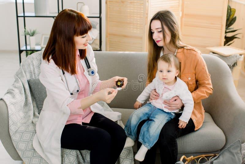 Ο γιατρός εγχώριων γυναικών στο άσπρο παλτό εξετάζει λίγο μωρό στο σπίτι ή στην κλινική Ο καλός θεράπων παθολόγων κοιτάζει δίνει  στοκ φωτογραφία