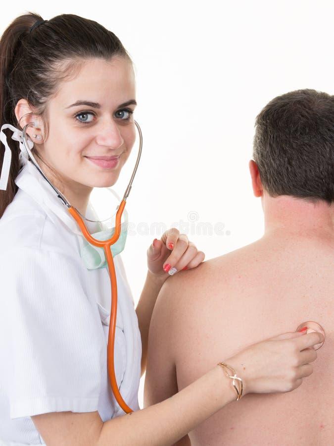 Ο γιατρός εξετάζει τον αρσενικό ασθενή με ένα στηθοσκόπιο στοκ φωτογραφία