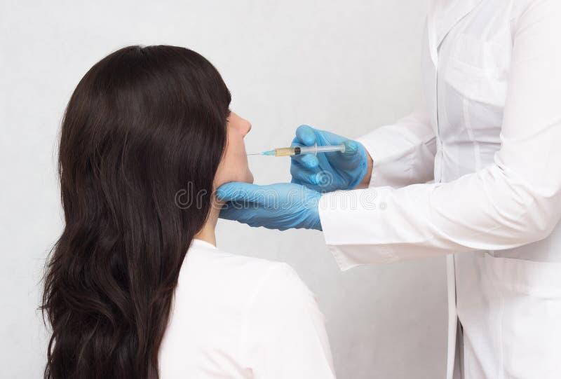 Ο γιατρός κάνει μια έγχυση με το πλάσμα αίματος ενός κοριτσιού ενάντια στην ακμή και το καλό δέρμα στο πρόσωπο, θεραπεία πλάσματο στοκ εικόνες