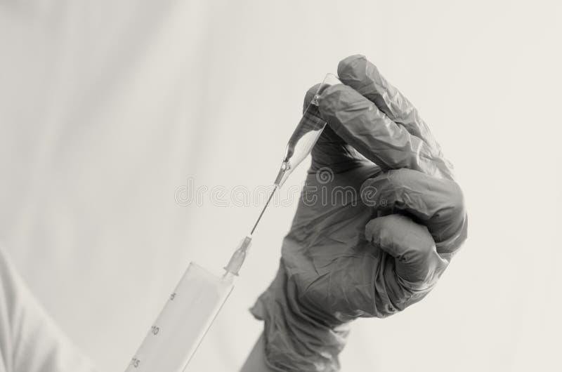 Ο γιατρός κάνει τις δοκιμές με ένα βιολογικό ρευστό στοκ εικόνες με δικαίωμα ελεύθερης χρήσης