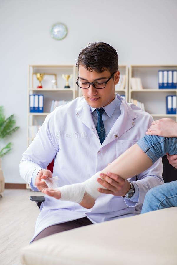Ο γιατρός και ο ασθενής κατά τη διάρκεια της εξέτασης για τον τραυματισμό στο νοσοκομείο στοκ φωτογραφία