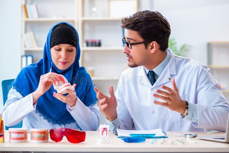 Ο γιατρός και ο βοηθός οδοντιάτρων που εργάζονται στο νέο μόσχευμα δοντιών στοκ φωτογραφίες με δικαίωμα ελεύθερης χρήσης