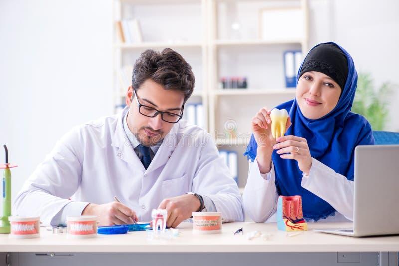 Ο γιατρός και ο βοηθός οδοντιάτρων που εργάζονται στο νέο μόσχευμα δοντιών στοκ φωτογραφίες