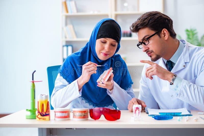 Ο γιατρός και ο βοηθός οδοντιάτρων που εργάζονται στο νέο μόσχευμα δοντιών στοκ εικόνες με δικαίωμα ελεύθερης χρήσης