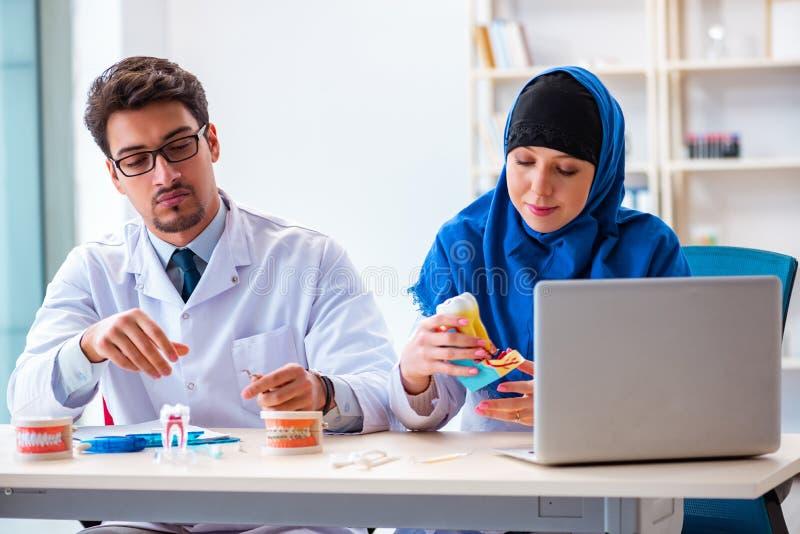 Ο γιατρός και ο βοηθός οδοντιάτρων που εργάζονται στο νέο μόσχευμα δοντιών στοκ φωτογραφία