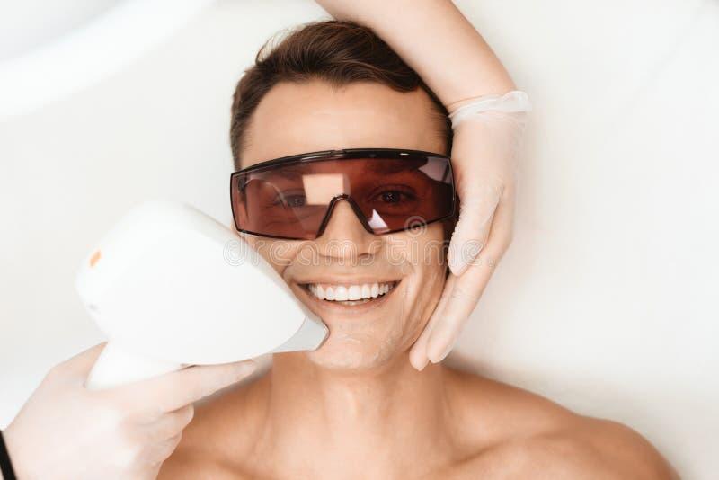 Ο γιατρός μεταχειρίζεται το πρόσωπο ενός ατόμου με ένα σύγχρονο epilator λέιζερ Το άτομο βρίσκεται και χαμογελά στοκ εικόνα