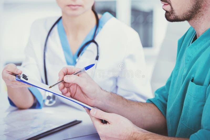 Ο γιατρός με το βοηθό παίρνει τις σημειώσεις στοκ εικόνες
