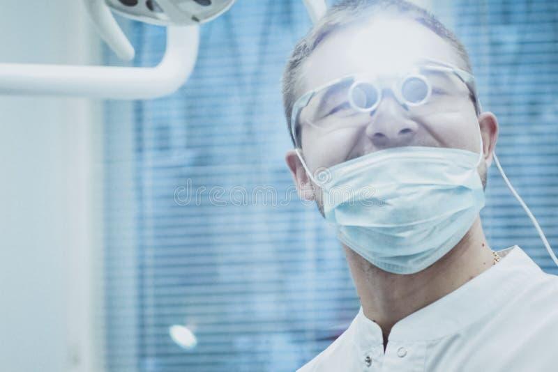 Στοματολογία Ο γιατρός οδοντιάτρων λάμπει στα μάτια μιας ειδικής συσκευής στοκ φωτογραφίες με δικαίωμα ελεύθερης χρήσης
