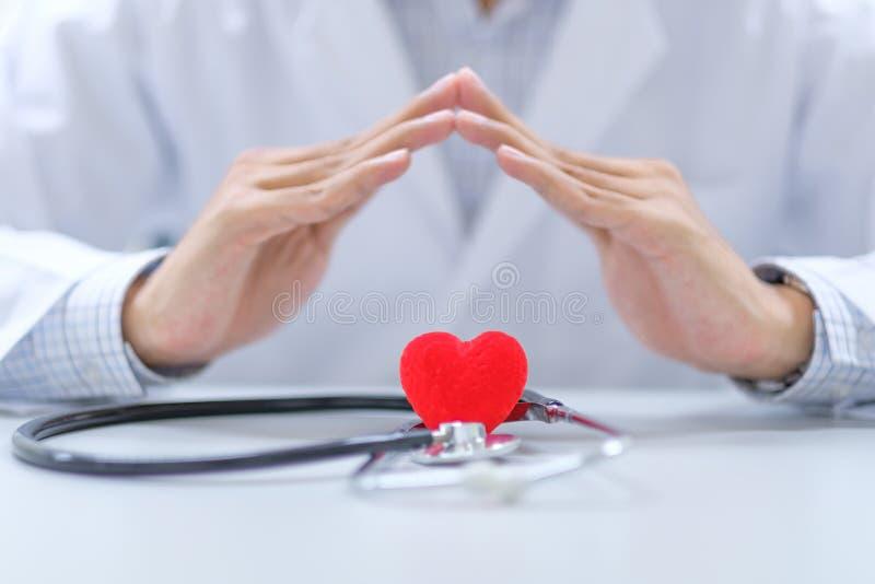 Ο γιατρός παραδίδει το στηθοσκόπιο και την κόκκινη μορφή καρδιών στο νοσοκομείο στοκ φωτογραφία με δικαίωμα ελεύθερης χρήσης