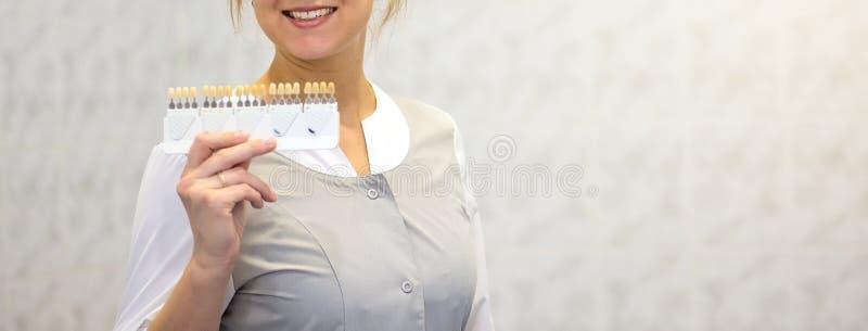 Ο γιατρός παρουσιάζει σκιές των κορωνών δοντιών σε μια ειδική παλέτα στοκ φωτογραφία με δικαίωμα ελεύθερης χρήσης
