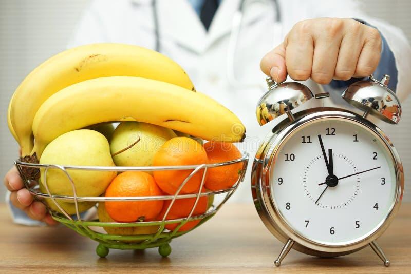 Ο γιατρός παρουσιάζει το ρολόι και φρούτα στον ασθενή για να αλλάξει την κατανάλωση του εκταρίου στοκ φωτογραφία με δικαίωμα ελεύθερης χρήσης