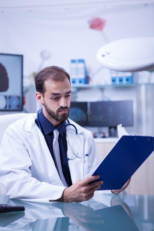 Ο γιατρός που εξετάζει το αποτέλεσμα αναλύει ενός ασθενή στην περιοχή αποκομμάτων του στοκ φωτογραφία με δικαίωμα ελεύθερης χρήσης