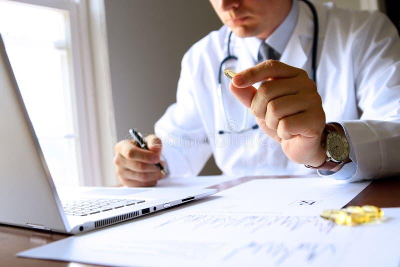 Ο γιατρός που εργάζεται σε έναν υπολογιστή στο γραφείο του και παρουσιάζει ένα χάπι στον ασθενή στοκ εικόνα