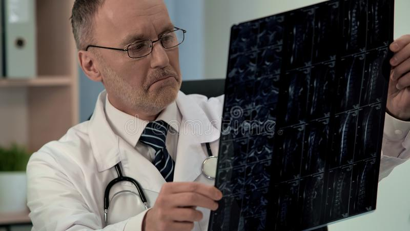 Ο γιατρός που μελετά το ανεπαρκές mri ασθενών, βρίσκει τη ζημία στον αυχενικό σπόνδυλο, διαγνωστικά στοκ φωτογραφία με δικαίωμα ελεύθερης χρήσης