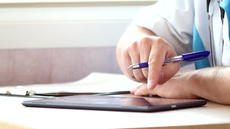 Ο γιατρός που χρησιμοποιεί μια ψηφιακή ταμπλέτα και γράφει τη συνταγή στοκ φωτογραφία με δικαίωμα ελεύθερης χρήσης