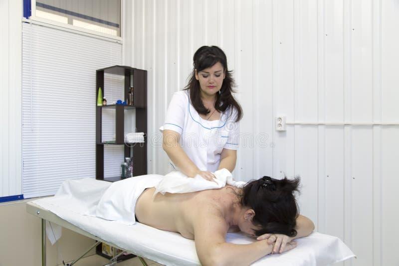 Ο γιατρός σκουπίζει την υπομονετική πλάτη ` s στοκ εικόνα με δικαίωμα ελεύθερης χρήσης
